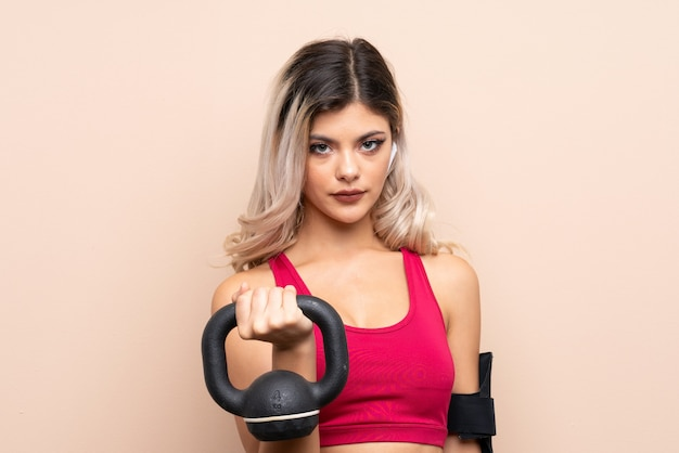 Jugendlichsportmädchen über dem lokalisierten hintergrund, der gewichtheben mit kettlebell macht und zur front schaut