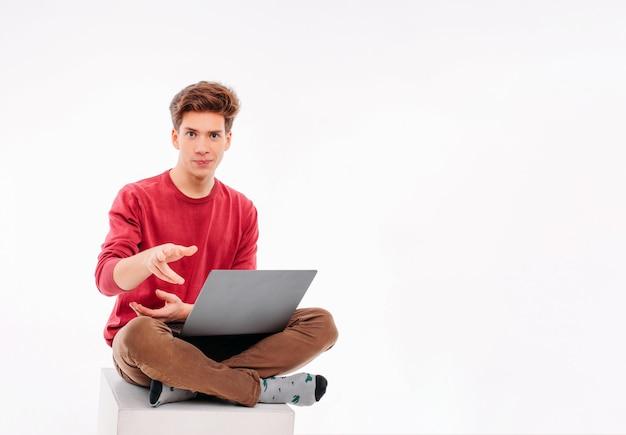 Jugendlichstudent, der am laptop auf weißem hintergrund arbeitet