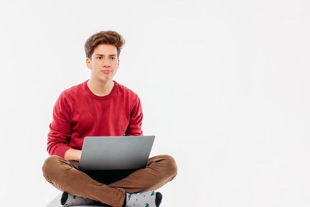 Jugendlichstudent mit dem lustigen gesicht, das am laptop auf weißrückseite arbeitet