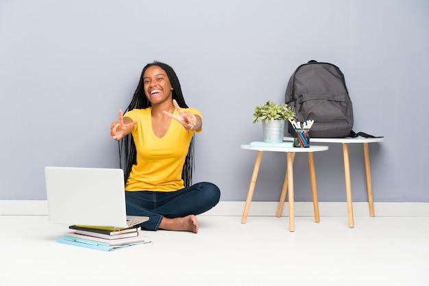 Jugendlichstudentenmädchen, das auf dem boden lächelt und siegeszeichen zeigt sitzt