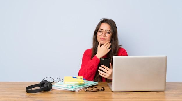 Jugendlichstudentenmädchen, das in einer tabelle denkt und eine mitteilung sendet studiert