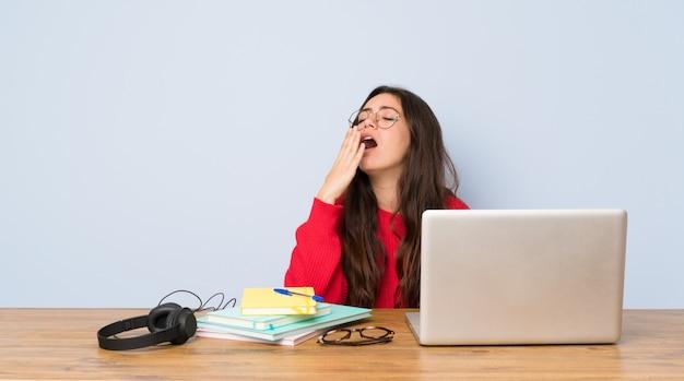 Jugendlichstudentenmädchen, das in einer tabelle gähnt und weit offenen mund mit der hand bedeckt studiert