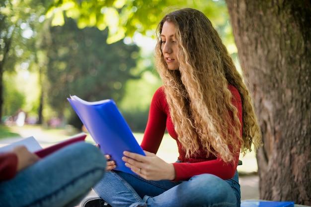 Jugendlichstudentin-lesebuch im park der schule