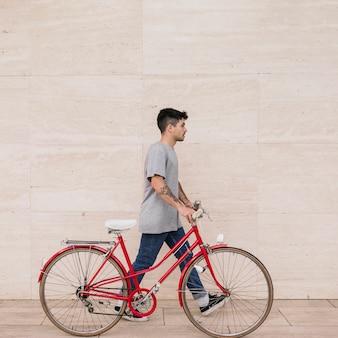 Jugendmann, der mit seinem fahrrad nahe wand geht