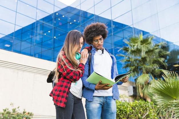 Jugendmann und studentinnen, die das buch stehen gegen das hochschulgebäude lesen