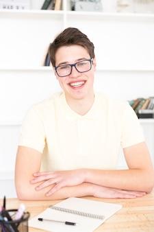 Jugendstudent, der am schreibtisch im klassenzimmer sitzt