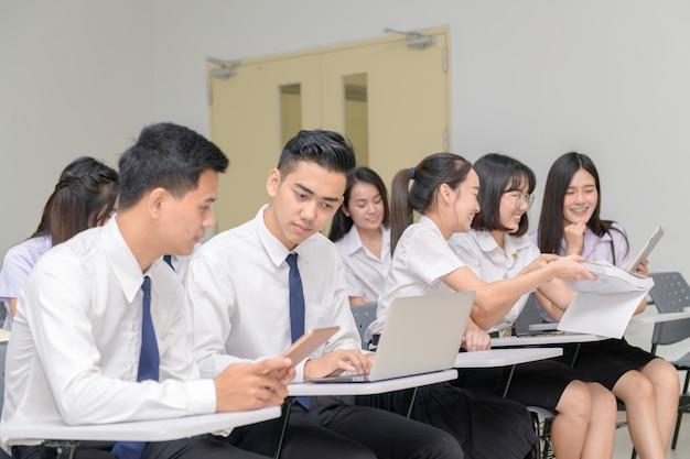 Jugendstudenten in der uniform, die mit laptop im klassenzimmer arbeitet
