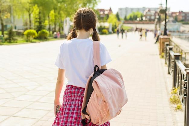 Jugendstudentenmädchen, das hinunter die straße mit rucksack geht