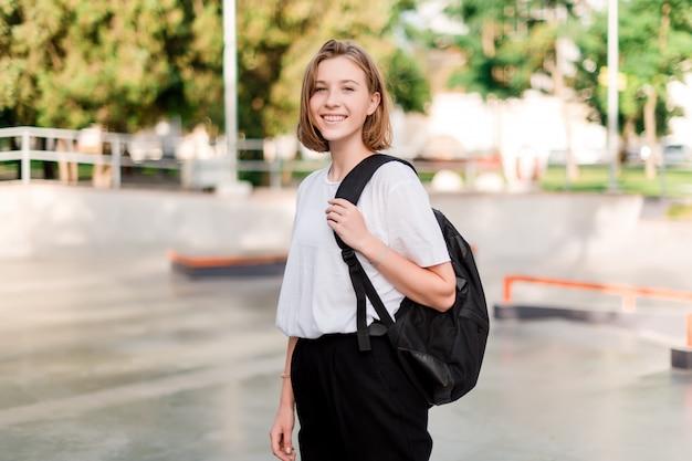 Jugendstudentenmädchen mit einer schultasche in einem park