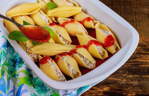 Jumbo-muschelnudeln gefüllt mit ricotta-käse und sauce marinara.