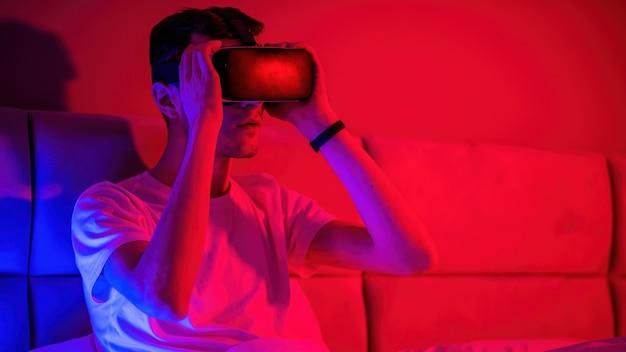 Jung beeindruckter mann in virtual-reality-brille mit blauer und roter beleuchtung im zimmer im bett. unterhaltung zu hause
