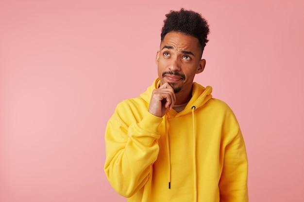 Jung denkender afroamerikaner kerl im gelben kapuzenpulli, schaut auf und berührt kinn, steht mit kopienraum.