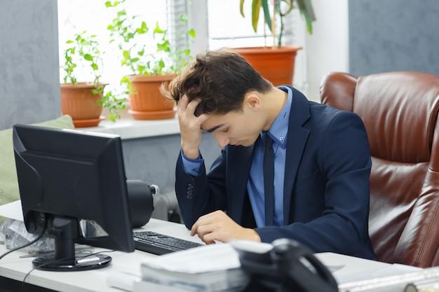 Jung frustriert mit problemen junger geschäftsmann, der am computer im büro arbeitet.