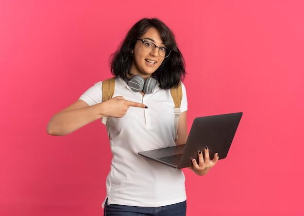 Jung überrascht hübsches kaukasisches schulmädchen mit kopfhörern am hals, brille und rückentasche hält und zeigt auf laptop auf rosa mit kopierraum
