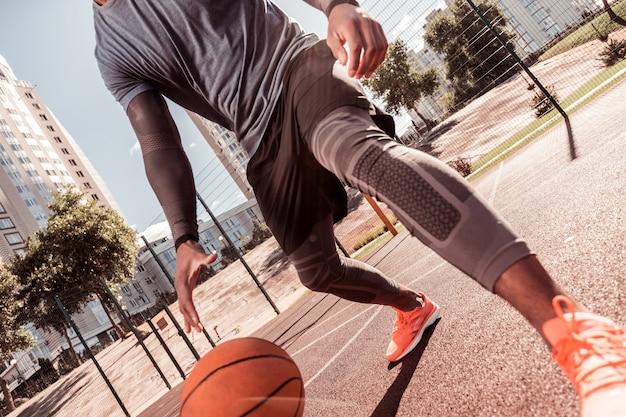 Jung und aktiv. netter gutaussehender mann, der sportspiele spielt, während aktiver lebensstil führt