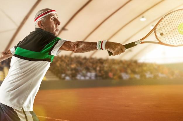 Jung und gesund bleiben älterer mann mit sportkleidung beim tennisspielen im stadion