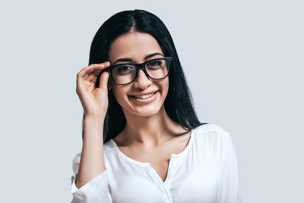Jung und klug. junge attraktive frau in weißem hemd und brille lächelnd im stehen vor grauem hintergrund