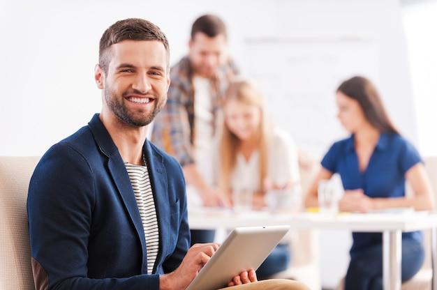 Jung und kreativ. hübscher junger mann, der ein digitales tablet hält und lächelt, während seine kollegen etwas im hintergrund diskutieren