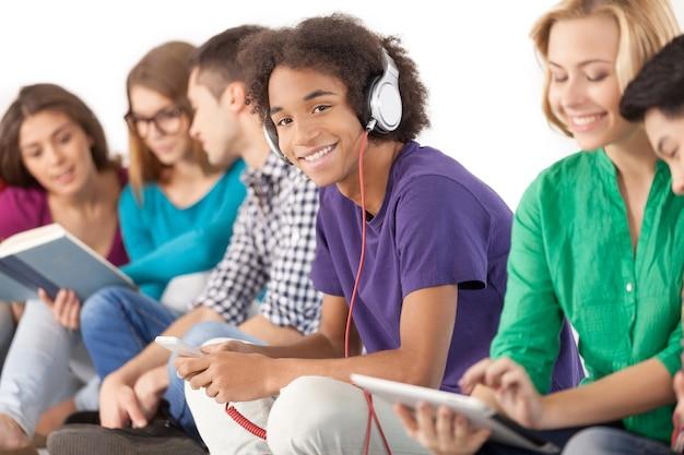 Jung und unbeschwert. gruppe multiethnischer studenten, die zeit zusammen verbringen, während sie isoliert auf weiß