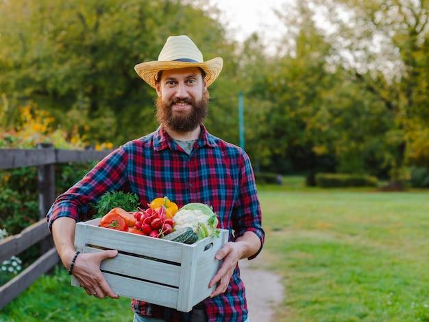 Junge 30-35 jahre alte junge bärtige mann männlich landwirt hut mit box frisch ökologisches gemüse gartensonnenuntergang.