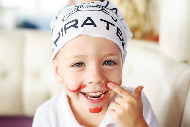 Junge 34 jahre alt in einem piratenbandana und rotem schnurrbart sieht in die kamera und lächelt