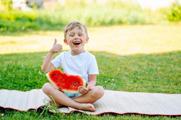 Junge 5 jahre alt isst draußen reife saftige wassermelone und zeigt daumen hoch. platz für text.