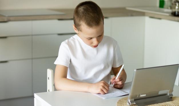 Junge 6-10 erledigt schulstunden und hausaufgaben online in der küche und schaut auf den tablet-computer. das konzept des fernunterrichts. bleib zuhause.