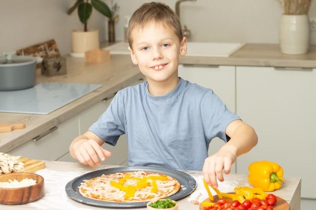 Junge 7-10 im t-shirt, das pizza in der küche kocht. kind lächelt und kocht