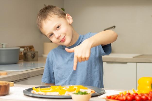Junge 7-10 im t-shirt, das pizza in der küche kocht, kind lächelt und zeigt finger auf pizza