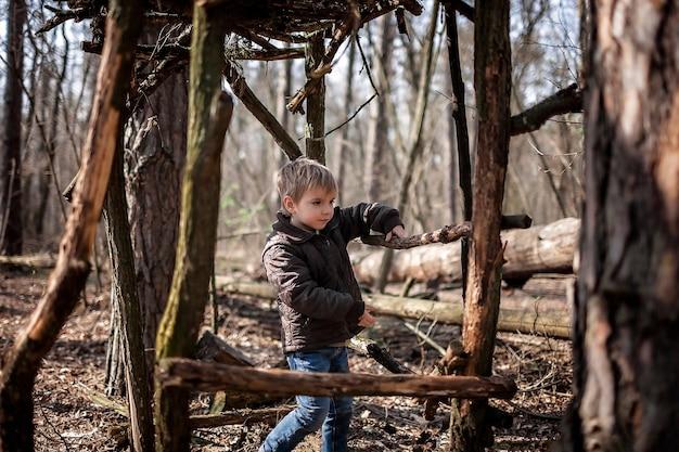 Junge abenteurer, die einen hölzernen lebensraum im wilden wald während des sozialen entfernten gehens bauen