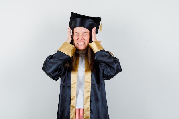 Junge absolventin, die hände in aggressiver weise in akademischer kleidung isoliert hält