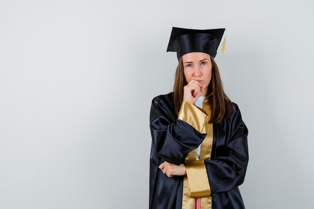 Junge absolventin, die im denken steht, posiert in akademischer kleidung und sieht nachdenklich aus. vorderansicht.