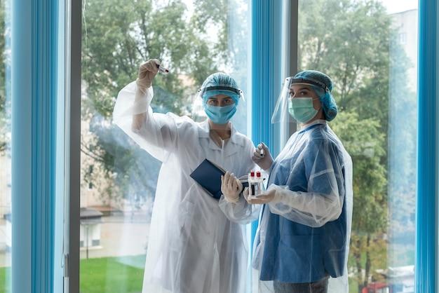 Junge ärzte erforschen reagenzgläser mit blutproben, um das in der klinik stehende coronavirus zu untersuchen