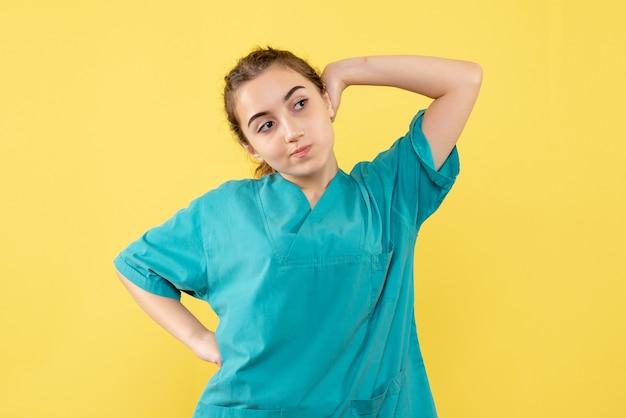 Junge ärztin der vorderansicht im medizinischen anzug auf gelbem hintergrund