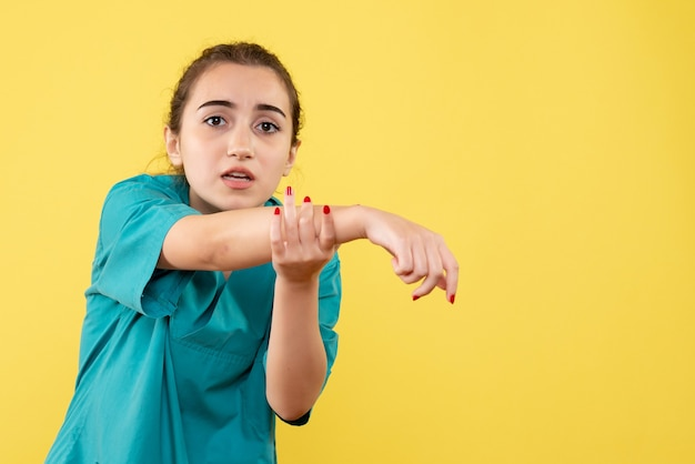 Junge ärztin der vorderansicht im medizinischen anzug mit verletzter hand auf gelbem hintergrund