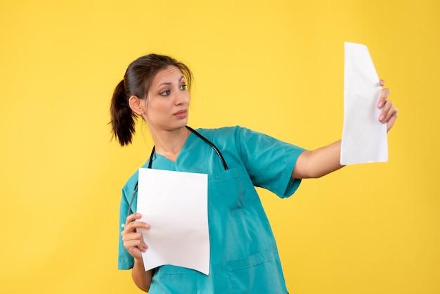 Junge ärztin der vorderansicht im medizinischen hemd, die papieranalyse auf gelbem hintergrund hält