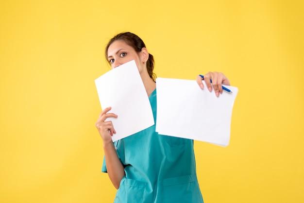 Junge ärztin der vorderansicht im medizinischen hemd mit papieren auf gelbem schreibtisch