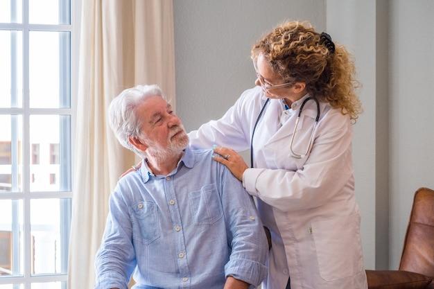 Junge ärztin, die älteren mann zu hause anregt. arzt hilft älteren patienten und kümmert sich. weibliche heimpflegerin, die sich um den alten mann im ruhestand kümmert. alter mann und arzt sprechen im pflegeheim
