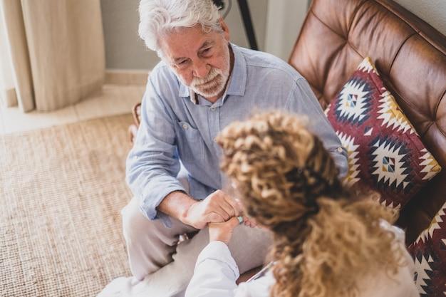 Junge ärztin, die älteren mann zu hause überprüft und hilft. arzt hilft älteren patienten und kümmert sich, sitzt auf dem sofa. heimpflegerin mit pensioniertem alten mann zu hause