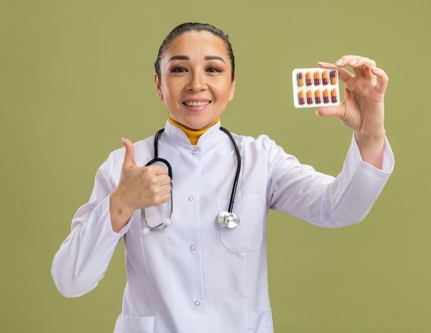 Junge ärztin, die blase mit pillen zeigt, die daumen nach oben lächelnd zeigt