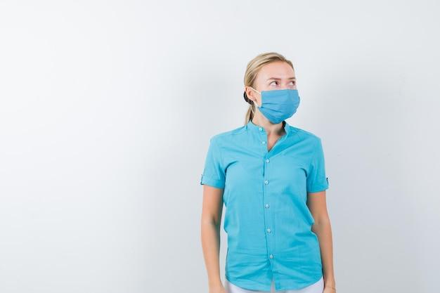 Junge ärztin, die in medizinischer uniform, maske und nachdenklichem blick wegschaut