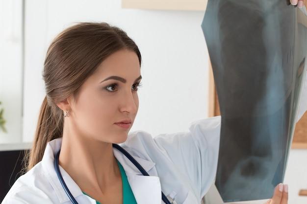 Junge ärztin, die lungen-röntgenbild betrachtet