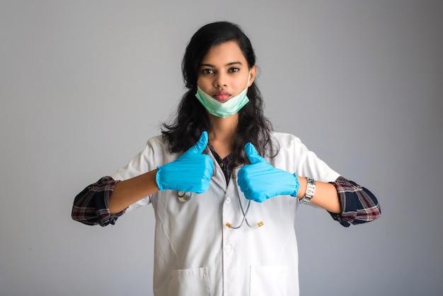 Junge ärztin, die medizinische gesichtsmaske trägt zeichen zeigend. doktorfrau, die chirurgische maske für koronavirus trägt.