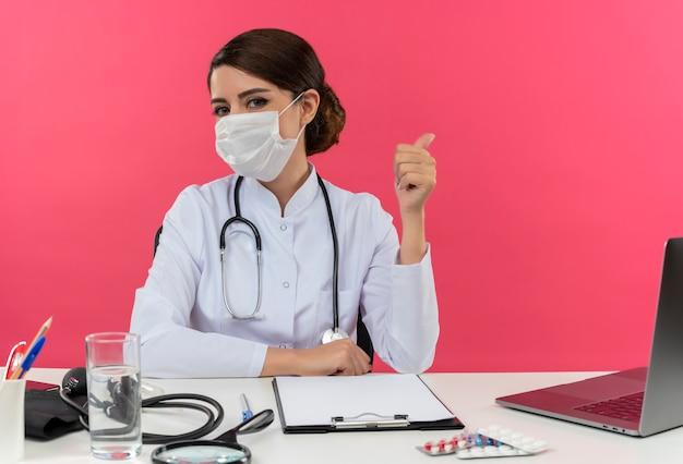 Junge ärztin, die medizinische robe mit stethoskop in der medizinischen maske trägt, die an der schreibtischarbeit am computer mit medizinischen werkzeugen sitzt, zeigt zur seite auf rosa wand mit kopienraum