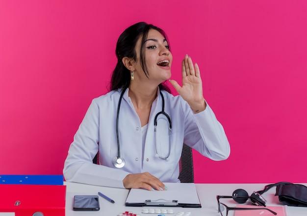 Junge ärztin, die medizinische robe und stethoskop trägt, die am schreibtisch mit medizinischen werkzeugen sitzt, die hand auf schreibtisch setzen, die seite betrachten, die hand in der luft hält, die zu jemandem ruft, der auf rosa wand isoliert wird