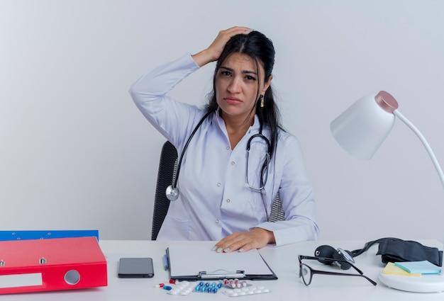 Junge ärztin, die medizinische robe und stethoskop trägt, sitzt am schreibtisch mit medizinischen werkzeugen, die hände auf schreibtisch und auf kopf stellend kopfschmerz suchen