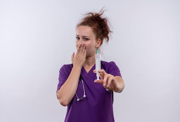 Junge ärztin, die medizinische uniform mit stethoskop hält, die spritze hält, schockierte, mund bedeckend mit hand, die über weiß steht