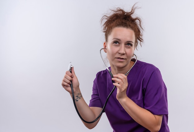 Junge ärztin, die medizinische uniform trägt, die leeren kopienraum mit nachdenklichem stethoskop über weißer wand hörend hört