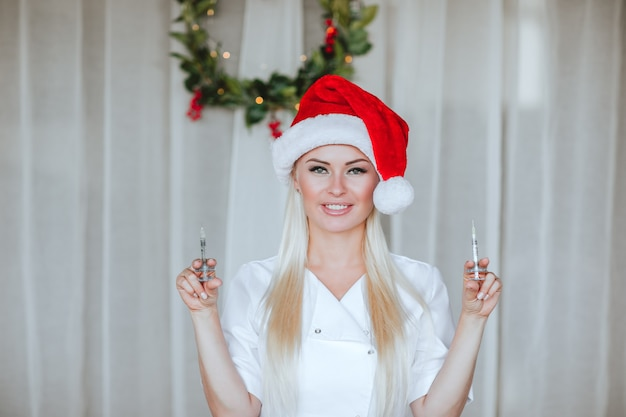 Junge ärztin, die mit spritzen auf weißem hintergrund mit weihnachtskranz aufwirft.