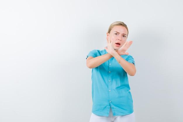 Junge ärztin, die stop-geste in medizinischer uniform, maske und angst zeigt